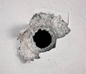 Mottoplakat: Schussloch in einer Wand