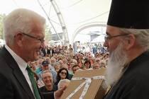 Als Dankeschön überreicht Erzpriester Radu Constantin Miron (re.) Ministerpräsident Kretschmann Frankfurter Wein